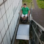 Photo showing a wheelchair user accessing the stair lift